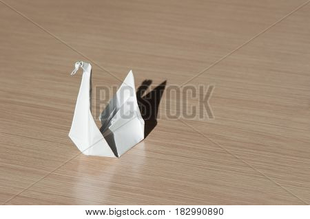 Origami bird on the table at sunny day