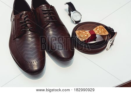 Wooden bow tie, brown leather shoes, belt, watch. Grooms wedding morning. Close up of modern man accessories. Close up of modern man accessories on a white background. Look from above