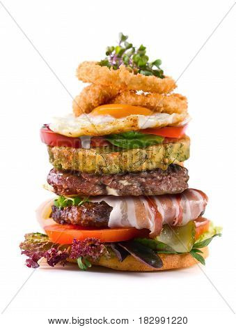 Big Burger with bacon meatballs fried egg onions tomatoes pickled cucumbers and salad . Isolated on white background .