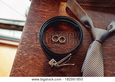 Close up of modern groom accessories. wedding rings, necktie, leather shoes and belt on the wooden table. Selective focus.