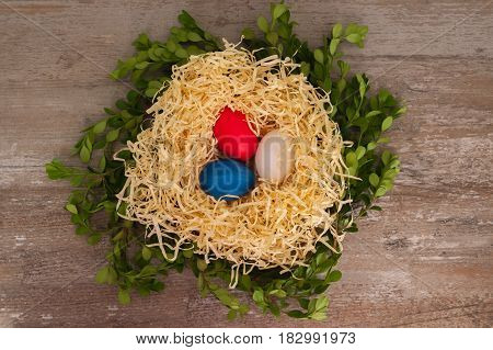 Easter tricolour eggs on a wooden background in the nest. Situated on the middle