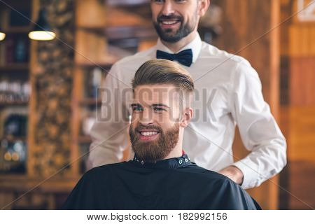 Young man sitting in a barbershop cheerful preparation for the haircut