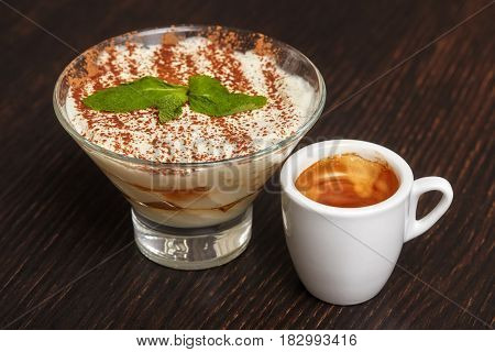 Tiramisu creme cake dessert in glass with mint leaves and coffee cup on black wooden background
