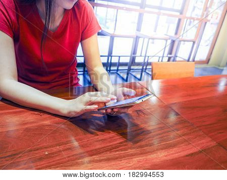 Asian woman is playing smartphone in restuarant