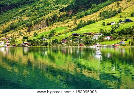Natural rural landscape. Town and cruise port Olden in Norwegian fjords. Tourist camping on the beach.