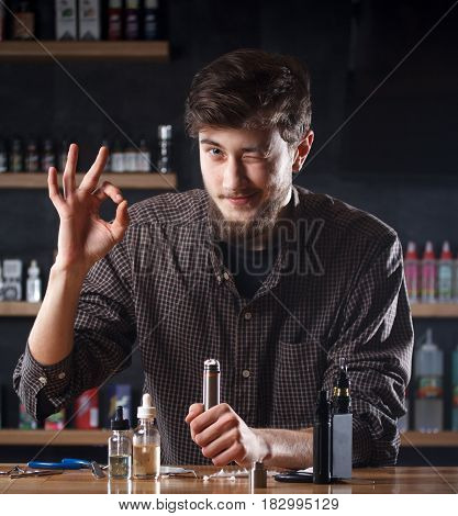 Vape Shop. A Man Is Holding A Mod In Hand And Shows