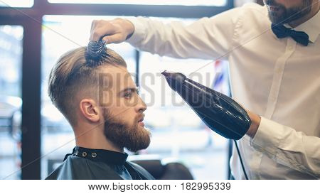 Young man sitting in a barbershop while barber blow drying the hair