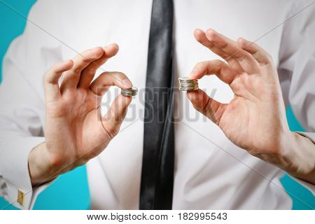 Close Up. Businessman Hands Compare Two Piles Of Coins Of Different Sizes, Indicating The Return On