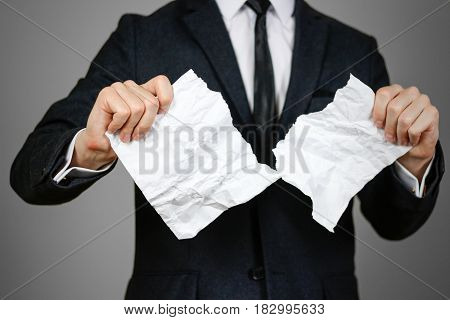 Businessman Tearing Hands Crumpled Sheet Of A4 Paper. Isolated On Grey Background