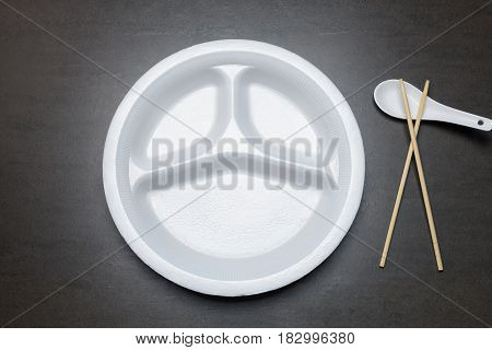 Empty disposable plastic plate on black table. White plate with three sections for food with spoon and bamboo chopsticks