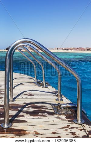 Level row Metallic chrome-plated Handrails railings on a yacht against the background of a sunny bright sky.