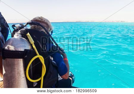 Woman with diving equipment looking at the sea.