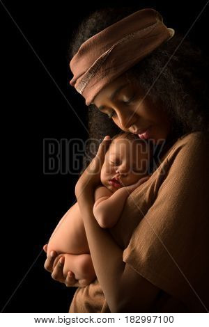 Ethiopian young mother holding her 7 days old little baby against a dark background