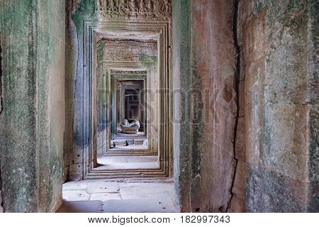 Long corridors and doorway of Prasat Bayon the central temple of Angkor Thom Complex, Siem Rea,p Cambodia. Ancient Khmer temple with frescoes and columns, World Heritage.