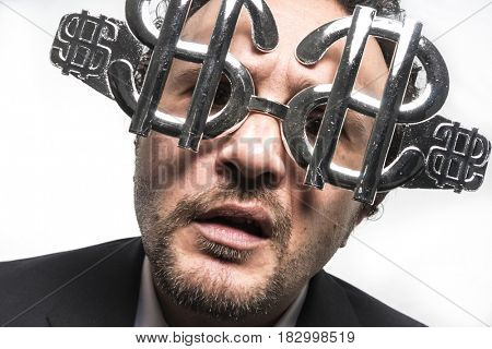 Concept Businessman with suit and glasses in the form of dollars. Expressions of stress, overwhelm and craving for money