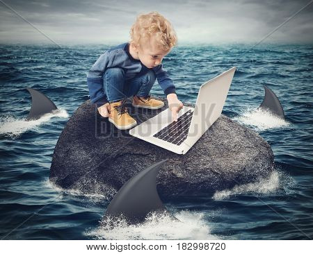 Child looks at the computer on a rock surrounded by sharks