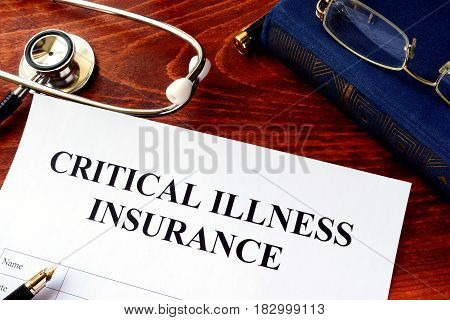 Critical illness insurance policy at the table.