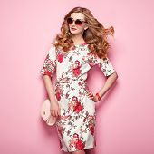 Blonde young woman in floral spring summer dress. Girl posing on a pink background. Summer floral outfit. Stylish wavy hairstyle. Fashion photo. Glamour lady in sunglasses with handbag poster