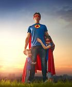 Happy loving family. Dad and his daughters are playing outdoors. Daddy and his children girls in an Superhero's costumes. Concept of Father's day. poster