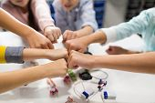 education, children, technology, science and people concept - group of happy kids with building kit making fist bump at robotics school poster