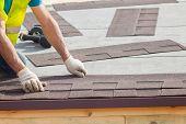 Roofer builder worker installing Asphalt Shingles or Bitumen Tiles on a new house under construction poster