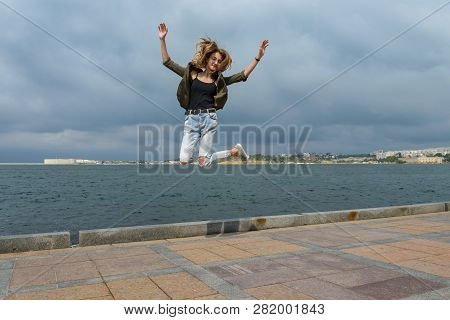 Young Girl In A Jump Shot Against The Sea
