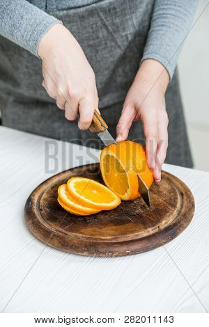 Woman Cuts Orange On Board Close Up View