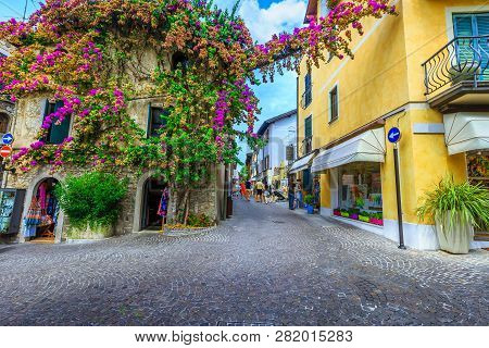 Sirmione, Italy - August 28, 2017: Amazing Colorful Purple Bougainvillea Flowers Around The Windows.