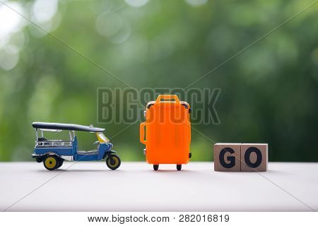 Miniature Tuk-tuk And Miniature Orange Suitcase With Wood Word Go, Travel In Thailand Image Concept