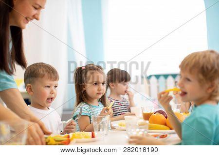 Kids And Carer Together Eat Fruits And Vegetables In Kindergarten Or Daycare
