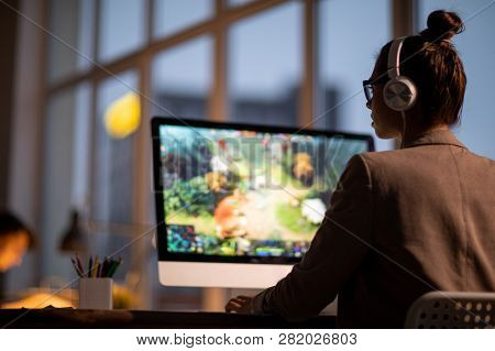 Young Female Colorist Or Footage Editor In Headphones Sitting In Front Of Computer Monitor With Vide