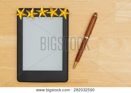 A Blank E-reader On A Desk With A Pen And Five Gold Stars That You Can Use As A Mock Up For Your Mes