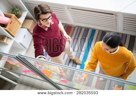 Overview Of Two Young Casual Office Workers Discussing Organization Notes On Sticky Notepapers On No