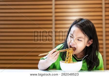 Asian Little Cute Girl Eating Delicious Instant Noodles With Chopstick By Herself On Wooden Curtain