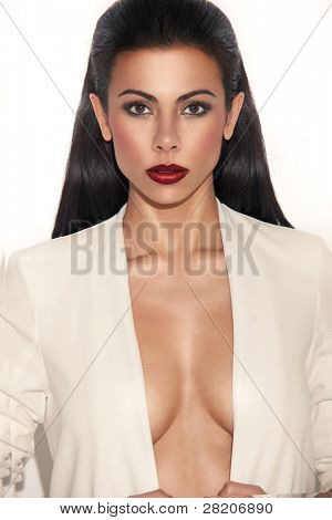 Glamorous busty woman with plunging neckline looking directly at camera, closeup on white