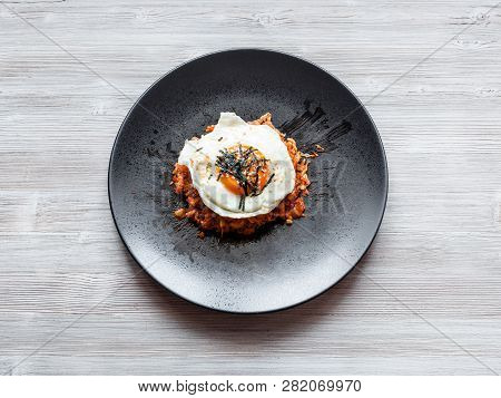 Korean Cuisine - Top View Of Kimchi Bokkeum Bap (fried Rice With Kimchi, Beef And Fried Egg) On Blac