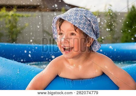 Cheerful Child In The Pool On Back Yard. Smiling Boy With Water Drops Around Spending Time In The Po