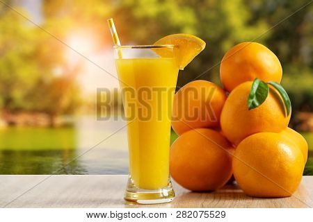 Tall Glass Of Tasty Freshly Squeezed Orange Juice Standing On An Outdoor Table With A Fresh Oranges.