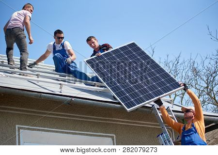Male Team Workers Installing Stand-alone Solar Photovoltaic Panel System. Four Electricians Lifting