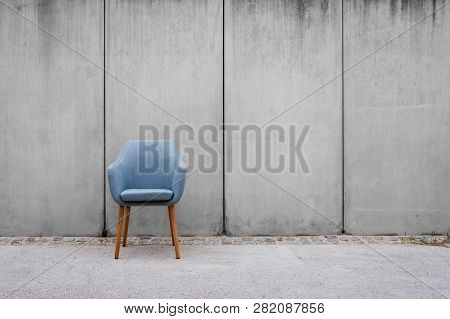 Chair And Blank Picture Frames On Sidewal With Concrete Wall Background