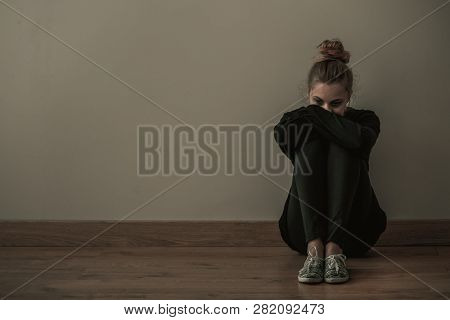 Young Woman With Anxiety Disorder Wearing Dark Clothes Sitting On The Floor, Copy Space On Empty Wal