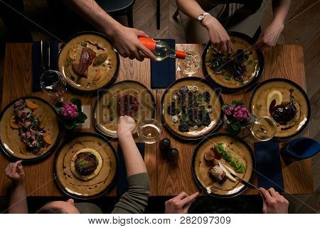 Company Gathering For Christmas Or New Year Party Dinner At Festive Table