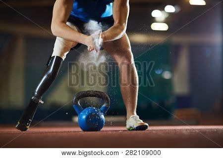 Paralympic competitor with handicapped leg standing on arena and applying powder on palms before lifting heavy kettlebell