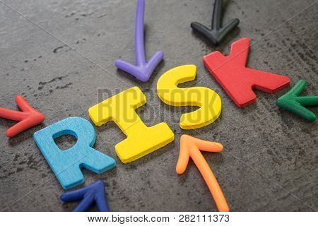 Colorful Arrows Pointing To The Word Risk At The Center Of Black Chalkboard Wall, Business Or Invest