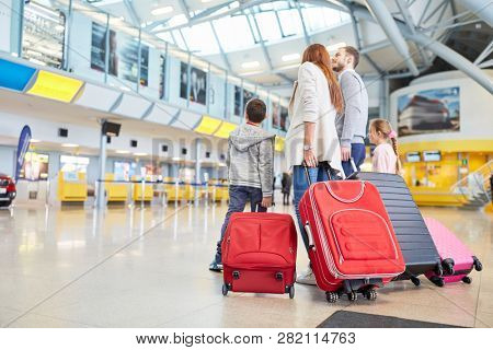Happy family and two children with luggage in the airport terminal are waiting for their departure