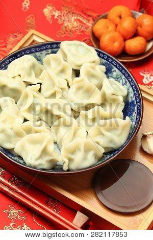 Chinese Jiaozi New Year Food, Spring Festival Dumplings On Traditional Spring Festival Red Backgroun