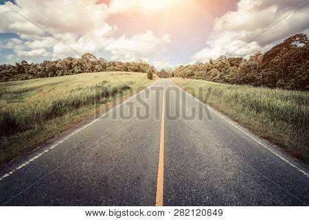 Highway Road Through Green Grass Under Blue Sky.