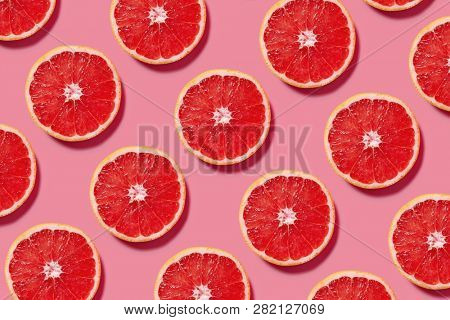 Colorful fruit pattern of fresh grapefruit slices on pink background. Minimal flat lay concept.
