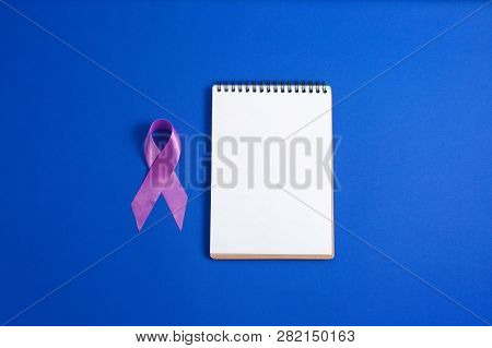 Purple Ribbons And Open Notebook On Blue Background, Alzheimer Disease, Pancreatic Cancer, Epilepsy
