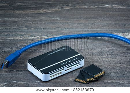 Close-up Image Of Card Reader And Three Memory Cards On Grey Wooden Background.